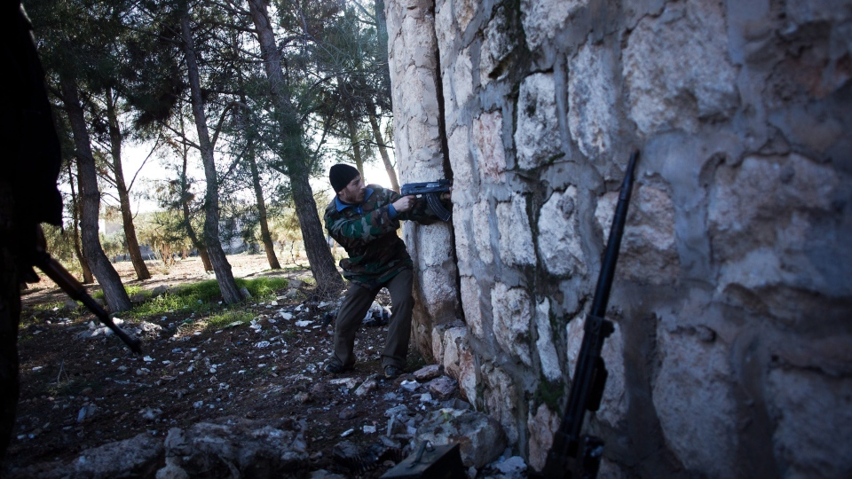 A Free Syrian Army fighter fires his machine gun toward Syrian Army positions during an assault to a military base in Tal Sheen, Syria, Saturday, Dec. 15, 2012. (AP / Manu Brabo)