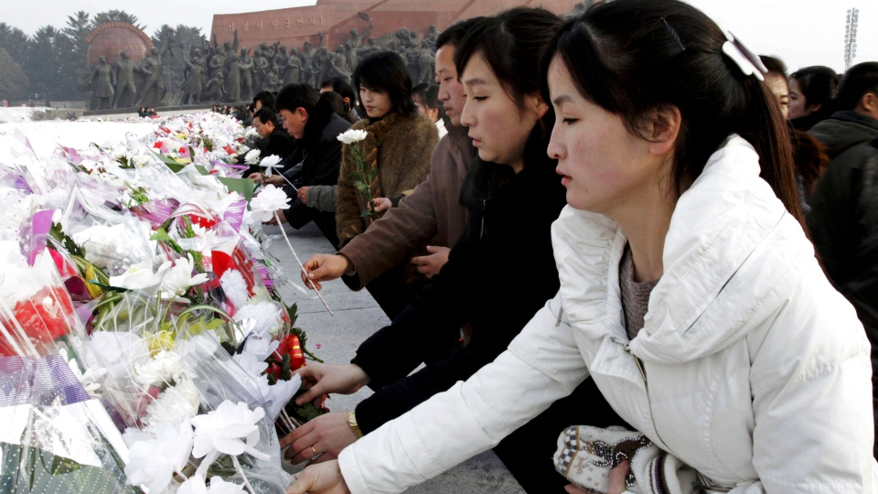 North Korean women lay flowers on Mansu Hill to show their respect to the late North Korean leaders Kim Il Sung and Kim Jong Il on the eve of the first anniversary of the death of Kim Jong Il in Pyongyang, North Korea on Sunday, Dec. 16, 2012 (AP / Jon Chol Jin)