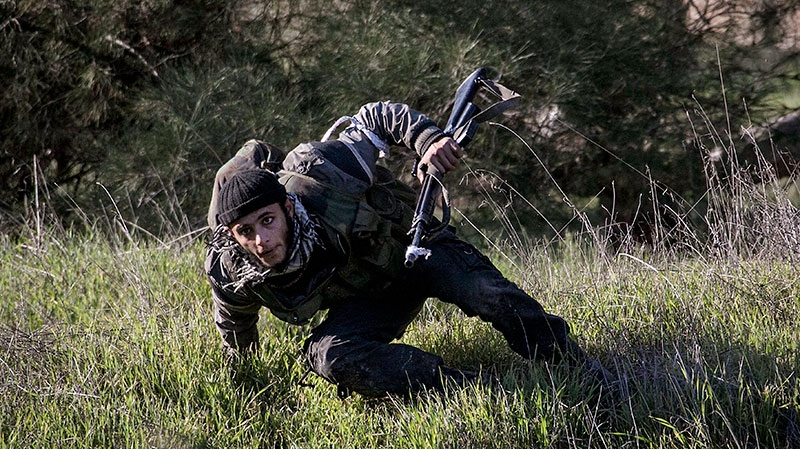 A Free Syrian Army fighter takes cover during heavy clashes with government forces at a military academy besieged by the rebels north of Aleppo, Syria, Saturday, Dec. 15, 2012. (AP / Narciso Contreras)