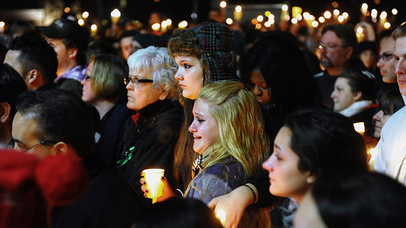 Stratford High School seniors Ally Kutzer and Caitlyn Larocque, centre front, attend a candlelight vigil with hundreds of other in memory of victims from the mass shooting in Newtown on the Town Hall Green in Stratford, Conn., Saturday, Dec. 15, 2012 (The Connecticut Post, Christian Abraham)