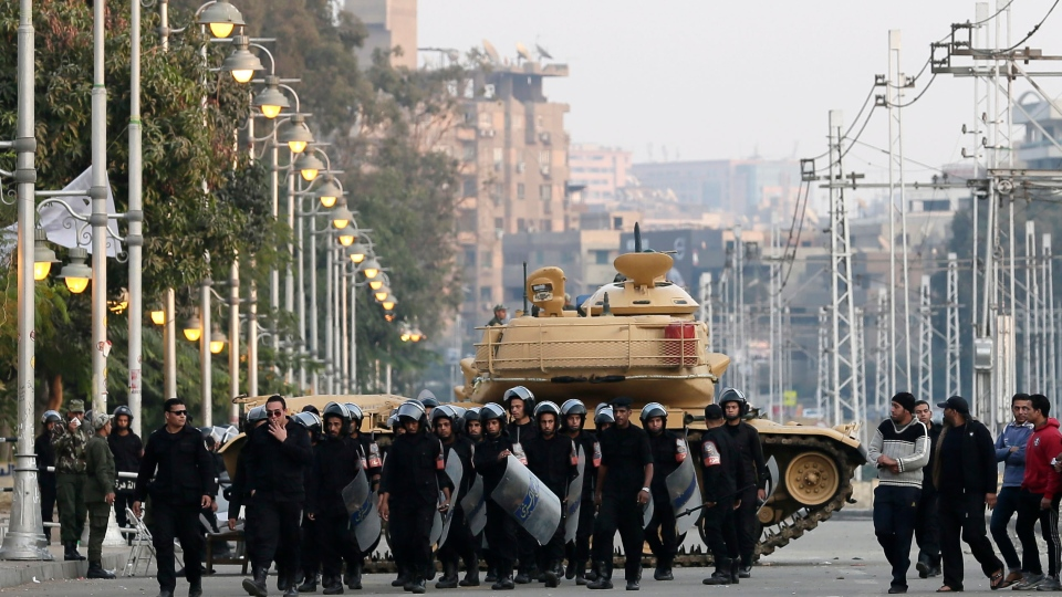 Egyptian riot police walk past a military tank guarding the presidential palace in Cairo, Egypt on Sunday, Dec. 16, 2012. (AP / Hassan Ammar)