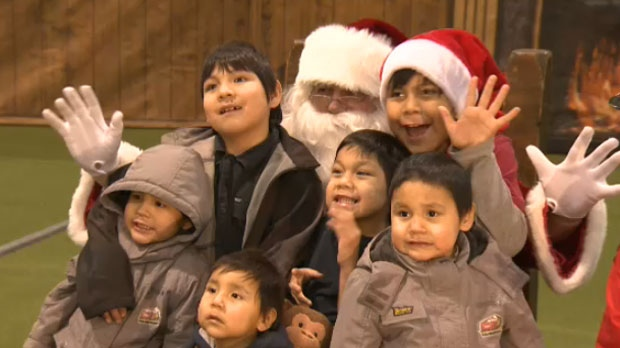 A group of children have their picture taken with Santa Claus at the Calgary Fire Department's Christmas Toy Party