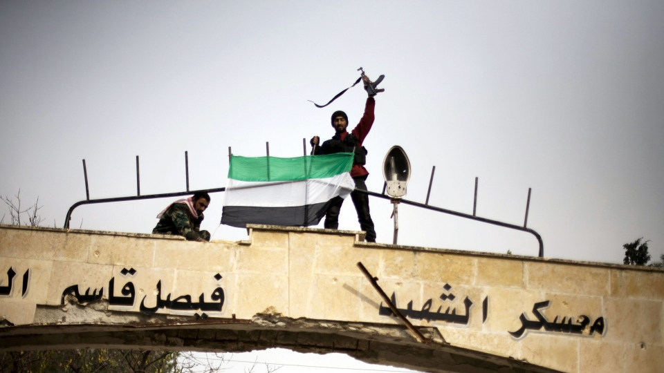 Free Syrian Army fighter puts up a FSA flag after heavy clashes with government forces at a military academy besieged by the rebels in Tal Sheer, Syria, Sunday, Dec 16, 2012. (AP / Manu Brabo)