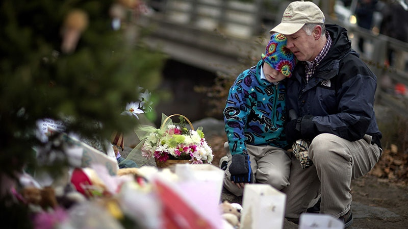 David Freedman, right, kneels with his son Zachary, 9, both of Newtown, Conn., as they visit a sidewalk memorial for the Sandy Hook Elementary School shooting victims, Sunday, Dec. 16, 2012, in Newtown, Conn.  (AP / David Goldman)