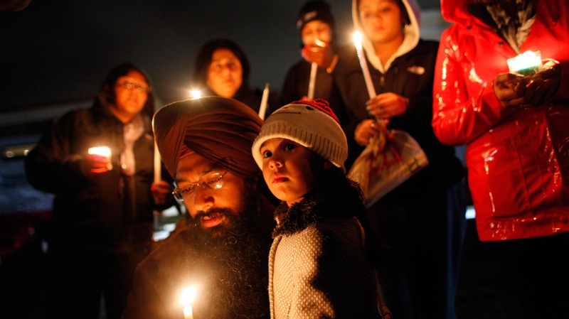 Eknoor Kaur, 3, stands with her father Guramril Singh during a candlelight vigil outside Newtown High School before an interfaith vigil with President Barack Obama, Sunday, Dec. 16, 2012, in Newtown, Conn.  (AP Photo/Jason DeCrow)