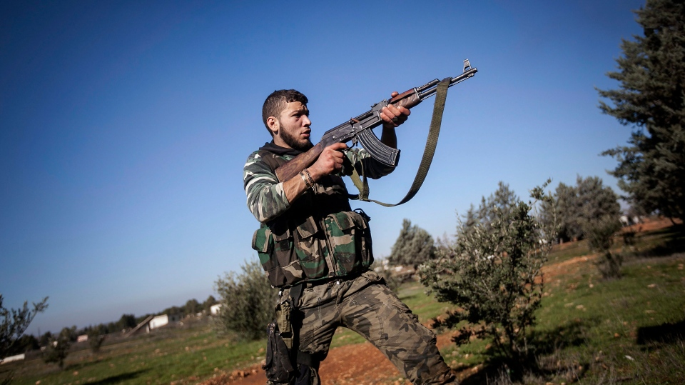 A Free Syrian Army fighter aims his weapon during heavy clashes with government forces at a military academy besieged by the rebels north of Aleppo, Syria Saturday, Dec. 15. 2012. (AP / Narciso Contreras)