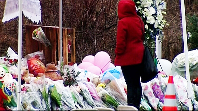 A mourner visits a memorial for the victims of the Sandy Hook school shooting ahead of the first funerals for victims on Monday, Dec. 17, 2012.