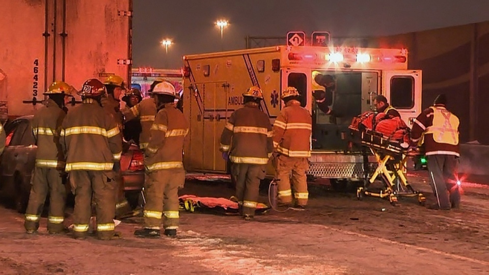 Paramedics load a crash victim into an ambulance while firefighters fight to remove more people from a sedan. The crash happened Sunday evening at the Anjou Interchange between Highways 25 and 40 in Montreal (Dec. 16, 2012. CTV Montreal/Cosmo Santamaria)