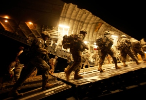 Soldiers from 2nd Brigade, 10th Mountain Division, board a C-17 aircraft at Baghdad International Airport as they begin their journey to the United States in this July 2010 file photo. (AP / Maya Alleruzzo)