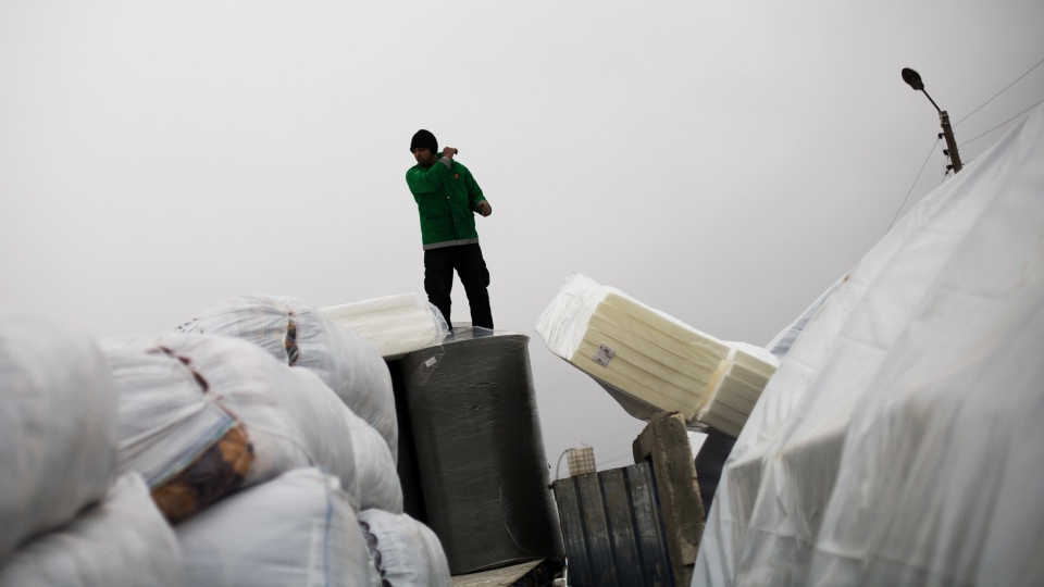 A worker from a Non Government Organization distributes mattresses to people at a refugee camp in Azaz, Syria, Monday, Dec. 17, 2012. (AP / Manu Brabo)