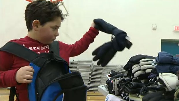 A student from George H. Luck Elementary School fills a backpack with gloves as part of the school's 'Backpacks of Luck' campaign to help the city's needy.