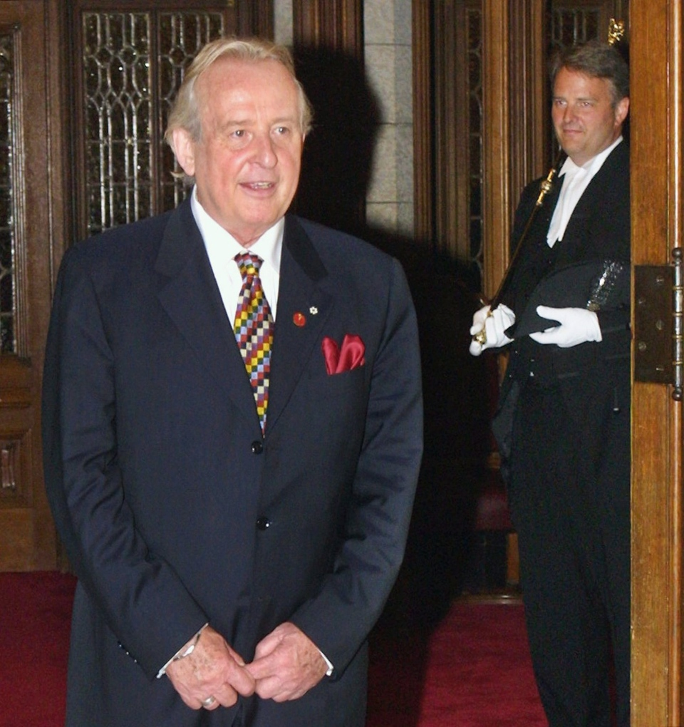 "Laurier LaPierre pauses for a photo outside the Senate prior to being sworn in during a ceremony on Parliament Hill in Ottawa Tuesday, Sept. 18, 2001. LaPierre, who gained fame as the co-host of CBC's ""This Hour has Seven Days,"" has died. (Jonathan Hayward/ THE CANADIAN PRESS)"