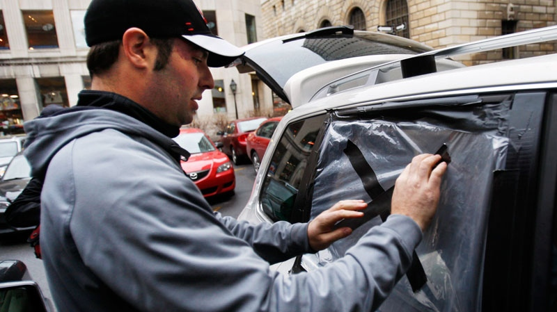 Jason Burns, son of former NHL coach Pat Burns, whose funeral was on Monday, tapes up the window of his mother's car  in Montreal Tuesday Nov. 30, 2010. (Ryan Remiorz / THE CANADIAN PRESS)