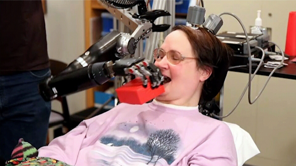 Ground-breaking technology allows 52-year-old Jan Scheuerman, who is paralyzed from the neck down, the ability to feed herself by controlling a robotic arm with her brain.