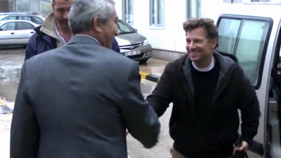 "NBC chief foreign correspondent Richard Engel, right, shakes hands with an unidentified person after crossing back into Turkey, after they were freed unharmed following a firefight at a checkpoint after five days of captivity inside Syria, in Cilvegozu, Turkey, Tuesday, Dec. 18, 2012. Engel told the Turkish news agency Anadolu that he and his colleagues are ""very happy to be out"" and they are ""very tired."" (Anadolu via AP TV)"