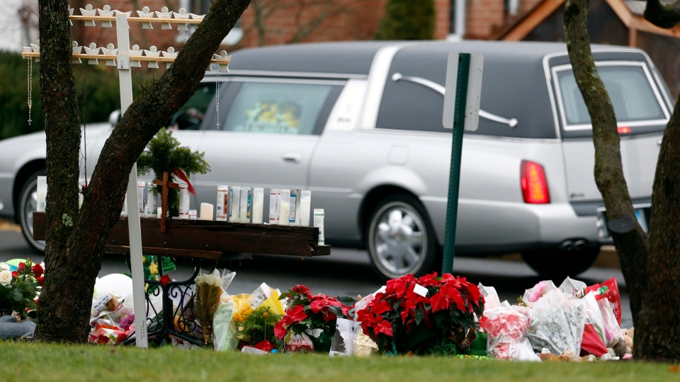 A makeshift memorial stands outside of St. Rose of Lima Roman Catholic Church as the hearse carrying the body of James Mattioli, Tuesday, Dec. 18, 2012, in Newtown, Conn. (AP / Julio Cortez)