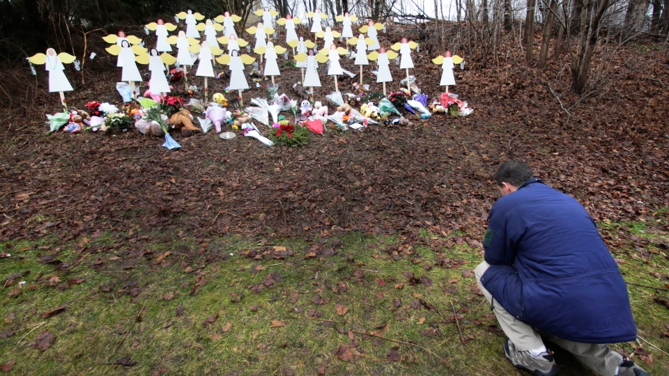Robert Soltis, of Newtown, Conn., pauses after making the sign of the cross at a memorial to school shooting victims in Newtown, Tuesday, Dec. 18, 2012. (AP / Charles Krupa)