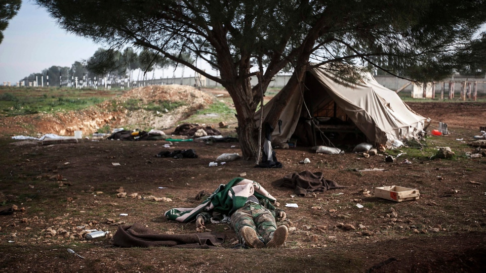 A lifeless body of a Syrian army soldier killed during heavy clashes with Free Syrian Army fighters is shown at a military academy besieged by rebels north of Aleppo, Syria, on Dec. 16, 2012. (AP / Narciso Contreras)