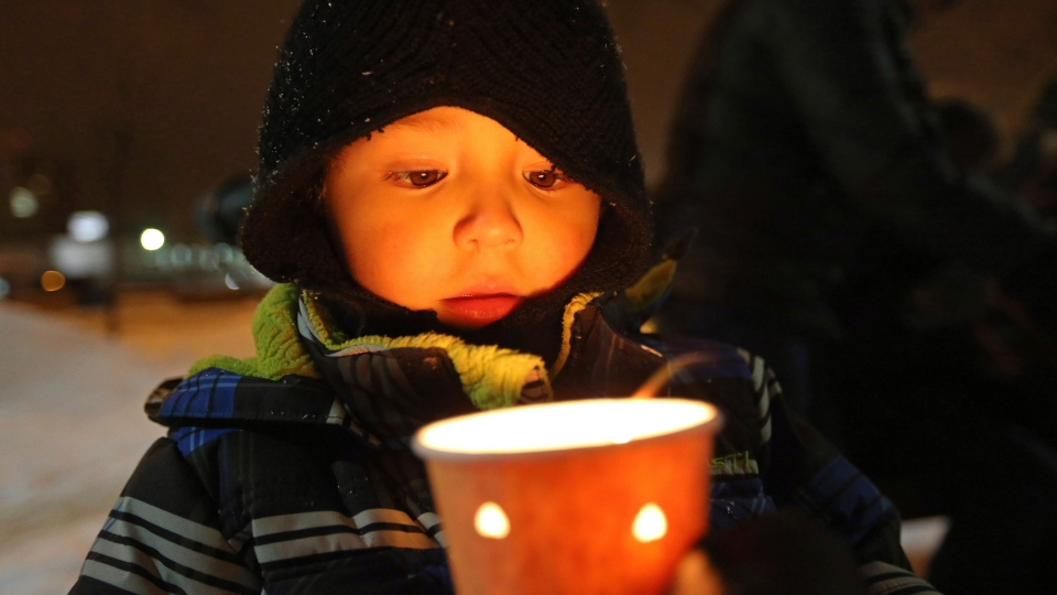 Lucas Gamez, 4, holds a candle at a vigil in memory of six year-old Ana Marquez-Greene, a victim of Friday's mass shooting in Newtown, Conn., on Monday December 17, 2012. (Trevor Hagan / THE CANADIAN PRESS)