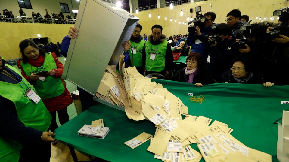 South Korean National Election Commission officials empty a box containing ballots for the presidential election in Seoul, South Korea, Wednesday, Dec. 19, 2012. Surveys released after polls closed in South Korea's hard-fought presidential election Wednesday indicated the race to replace unpopular incumbent Lee Myung-bak was too close to call. (AP Photo/Lee Jin-man)