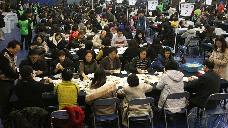 South Korean National Election Commission officials sort out ballots cast in the presidential election as they begin the counting process in Seoul, South Korea, Wednesday, Dec. 19, 2012. (AP / Ahn Young-joon)