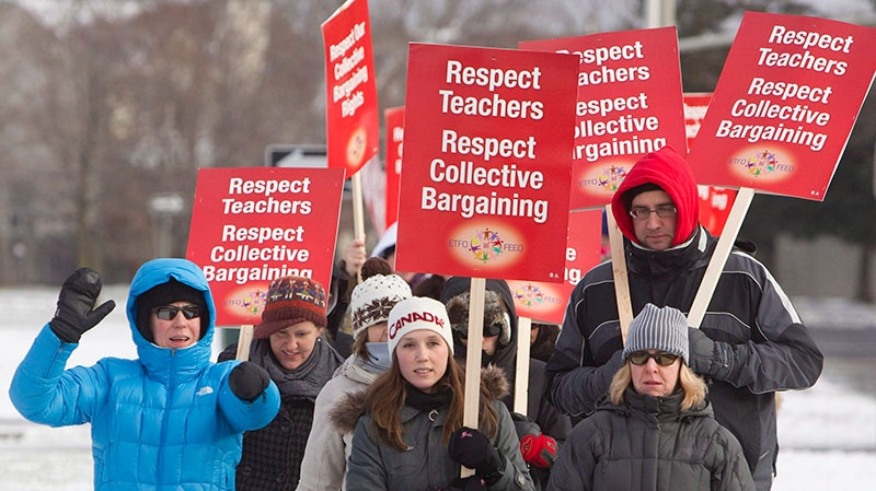 Continuing the wave of one-day walkouts, teachers of the Ottawa-Carleton District School Board carry picket signs at Roberta Bondar Public School in protest to Ontario's Bill 115, Wednesday, Dec. 12, 2012 in Ottawa. (Cole Burston / THE CANADIAN PRESS)