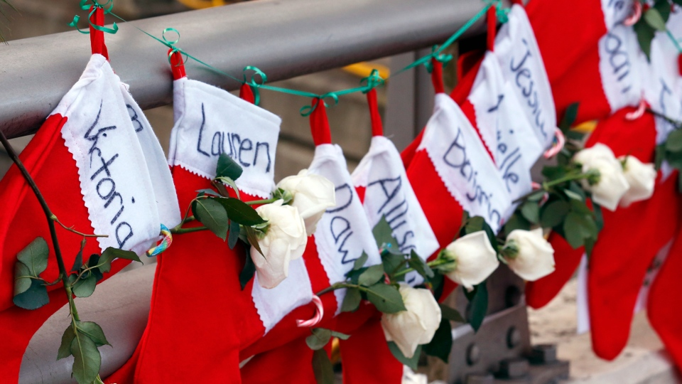 Christmas stockings with the names of shooting victims hang from railing near a makeshift memorial near the town Christmas tree in the Sandy Hook village of Newtown, Conn., Wednesday, Dec. 19, 2012. The memorial, which was put up in the aftermath of the elementary school shooting that shocked the small town, is increasing in size as the days go on. (AP / Julio Cortez)