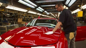 A worker checks the paint on a Camaro at the GM factory in Oshawa, Ont., in 2011. (Frank Gunn/THE CANADIAN PRESS)