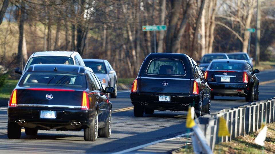 A hearse, centre, drives in a procession following funeral services for Charlotte Helen Bacon, one of the students killed in the Sandy Hook Elementary School shooting last week, at Christ the King Lutheran Church,  in Newtown, Conn., on Wednesday, Dec. 19, 2012. (AP / Julio Cortez)