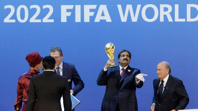 Sheikh Hamad bin Khalifa Al-Thani, Emir of Qatar, 2nd right, holds the World Cup trophy beside FIFA President Joseph Blatter after the announcement of Qatar hosting the 2022 soccer World Cup in Zurich, Switzerland, Thursday, Dec. 2, 2010. (AP / Anja Niedringhaus)