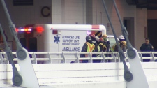Construction workers stand beside an ambulance after the injury of a fellow worker at Canada Place on Dec. 2, 2010. (CTV)