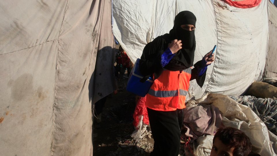 A Pakistani female health worker visits Lahore's slums to administer the polio vaccine to infants in Pakistan on Wednesday, Dec. 19, 2012. (AP / K.M. Chaudary)