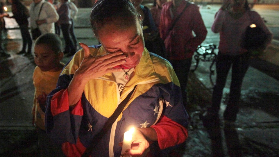 A woman holds a candle as she reacts during a vigil in support of Venezuela's President Hugo Chavez in Caracas, Venezuela, Thursday, Dec. 13, 2012. (AP / Fernando Llano)