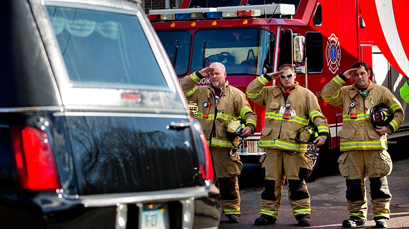 Firefighters salute as a hearse passes for the funeral procession to the burial of 7-year-old Sandy Hook Elementary School shooting victim Daniel Gerard Barden, in Newtown, Conn., Wednesday, Dec. 19, 2012. (AP / David Goldman)