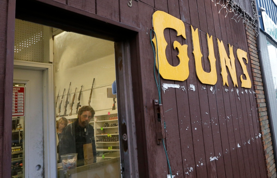 Rifles line a wall above in front of people standing in a gun shop in Seattle on Dec. 19, 2012. (AP Photo/Elaine Thompson)