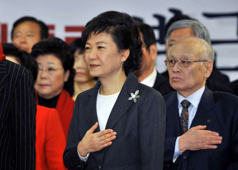 South Korea's president-elect Park Geun-hye, centre, salutes the national flag during a ceremony to disband her election camp at her party's headquarters in Seoul, South Korea, on Thursday, Dec. 20, 2012. (AP / Jung Yeon-je)