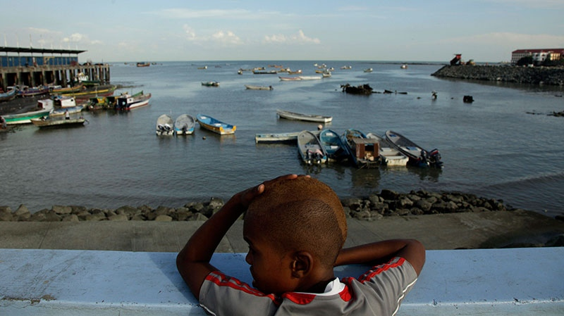 Ariel Alexis Cajar, 12, from Saboga Island, looks at fishing boats anchored at the Panama bay in Panama City, Wednesday, Dec. 19, 2012. (AP / Arnulfo Franco)