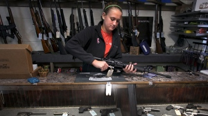 Atlas Tactical co-owner/operator Brooke Stallings handles an assault rifle that is for sale in her shop near Newport, Va. on Tuesday Dec. 18 2012. (AP / The Roanoke Times, Matt Gentry)