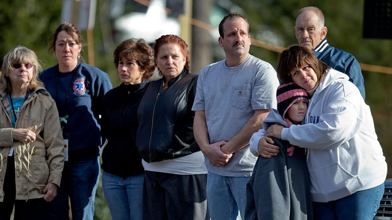 Mourners watch as the funeral procession of 7-year-old Sandy Hook Elementary School shooting victim Daniel Gerard Barden, passes the fire station outside the school's entrance, Wednesday, Dec. 19, 2012, in Newtown, Conn. (AP / David Goldman)