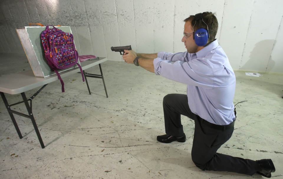 Rick Brand, Chief Operating Officer of Amendment II, shoots a 9 mm pistol into a children's backpack, left, fitted with an anti-ballistic insert during a demonstration at a gun range on Dec. 19, 2012. Anxious parents reeling in the wake the Connecticut school shooting are fueling sales of armored backpacks. (AP Photo/Rick Bowmer)