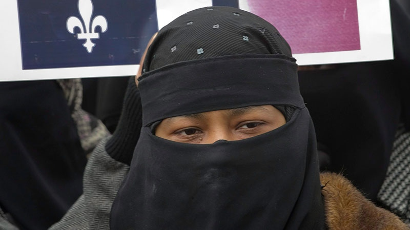 A woman wearing a niqab demonstrates in front of Montreal City Hall, protesting Bill 94, the Quebec Government tabled to require people to uncover their faces to identify themself in order to receive government services on Saturday, April 17, 2010. (Peter McCabe / THE CANADIAN PRESS)