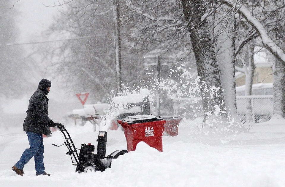 Laurie Molle snowblows her driveway on Dec. 20, 2012 at her home on Seventh Street in Goodview, Minn. (AP/Winona Daily News/Andrew Link)