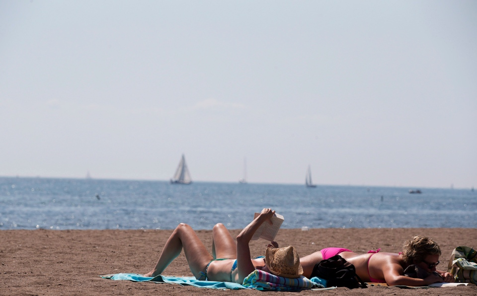People read as they sunbathe on a warm summer day at Cherry Beach in Toronto on Thursday, Aug. 23, 2012. (Michelle Siu / THE CANADIAN PRESS)