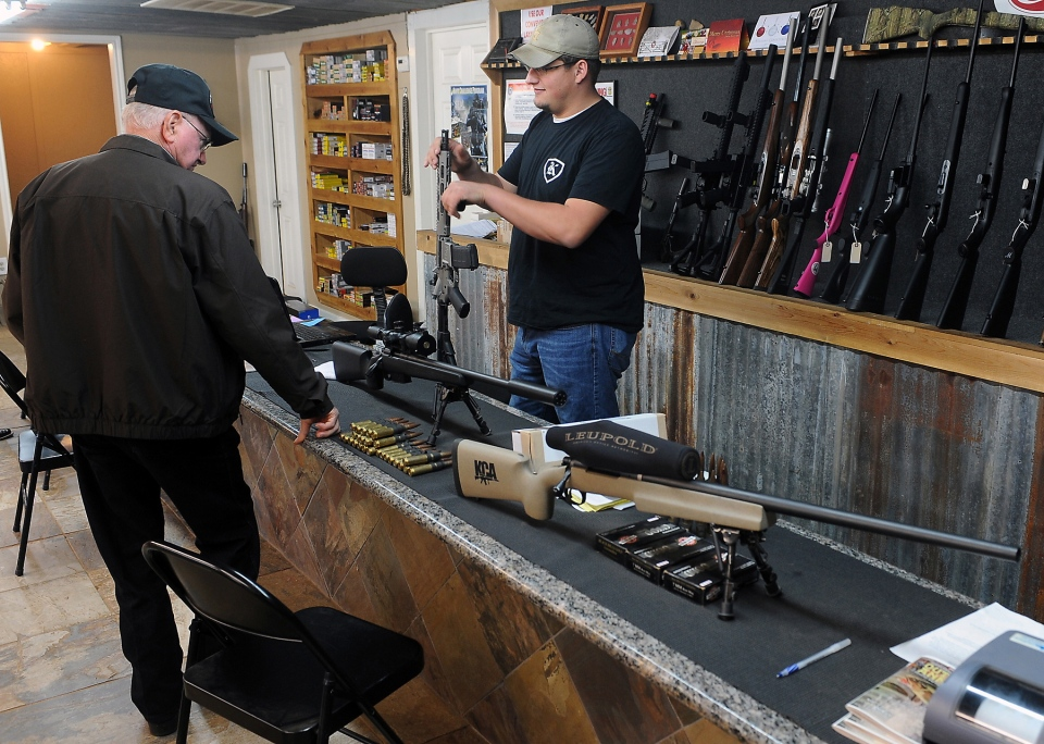Clerk Lance McCoy, right, shows a variety of weapons, including an AR-15 style semi-automatic at Kizer Guns and Ammo near Nacogdoches, Texas, Thursday, Dec. 20, 2012. (AP / The Daily Sentinel, Andrew D. Brosig)