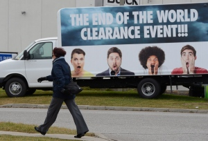 "A woman walks past a sign advertising an ""End of the World"" sale at a car dealership in Mississauga, Ont., on Thursday, Dec.20, 2012. (Frank Gunn / THE CANADIAN PRESS)"