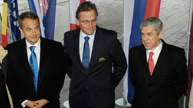 Portuguese Prime Minister Jose Socrates, right, and Spanish Prime Minister Jose Luis Rodriguez Zapatero, left, pose with FIFA General Secretary Jerome Valcke, center, as they and the delegation arrive at the FIFA headquarters in Zurich, Switzerland, Thursday, Dec 2, 2010, to present their bid to host the soccer World Cup 2018. (AP / Keystone, Steffen Schmidt)