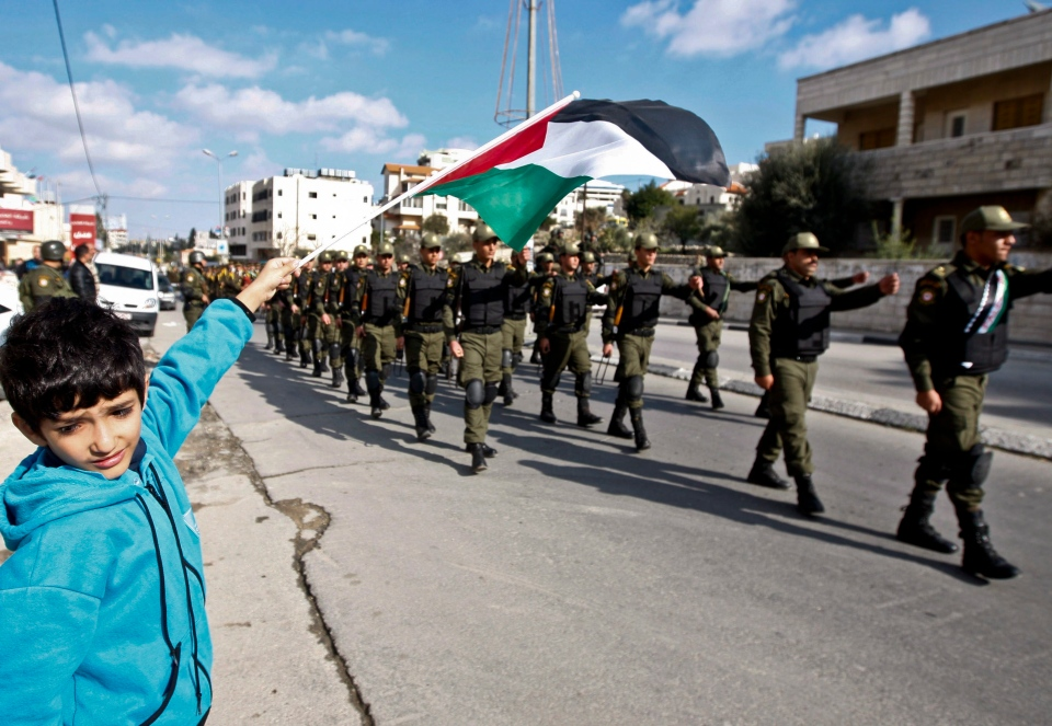 A Palestinian youth waves a flag as security officers march in support of Palestinian President Mahmoud Abbas, and to celebrate their successful bid to win U.N. statehood recognition the in the West bank city of Bethlehem, Monday, Dec. 17, 2012. (AP / Majdi Mohammed)