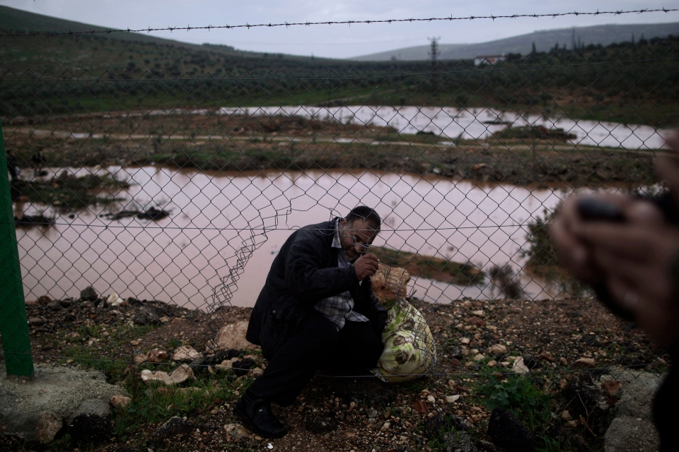 A Syrian refugee, crosses illegally to Turkey on the border fence, in Cilvegozu, Turkey, Thursday, Dec. 20, 2012. (AP Photo/Muhammed Muheisen)