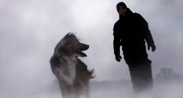 Zach Stead and his dog Tucker brave high winds, blowing snow and freezing temperatures while walking outside Thursday, Dec. 20, 2012 in Springfield, Ill.  (AP / Seth Perlman)