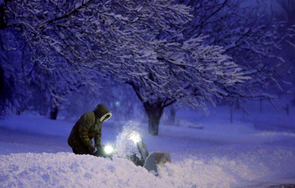 A local resident clears snow from his driveway after an overnight snowfall left many schools and businesses closed for the day, Thursday, Dec. 20, 2012, in Urbandale, Iowa. (AP / Charlie Neibergall)